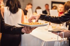 Woman taking snacks from the waiter on a fashion event party. Catering service concept. stock photography