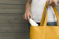 Woman taking sun screen, hand cream out of yellow purse. Sun pro royalty free stock image