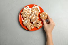 Woman taking tasty homemade Christmas cookie from plate Royalty Free Stock Photography