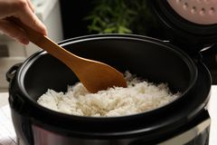 Woman taking tasty rice with spoon from cooker in kitchen stock image