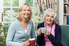 Woman Taking Time To Visit Senior Female Neighbor And Talk Royalty Free Stock Photo