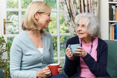 Woman Taking Time To Visit Senior Female Neighbor And Talk Stock Image