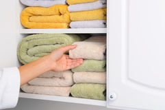 Woman Taking Towel From Linen Closet. Closeup of a womans hand taking a towel from a linen closet. Arm is partially covered by her bathrobe. Horizontal format royalty free stock photo