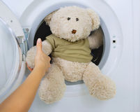 Woman taking toy from washing machine. Woman taking fluffy toy from washing machine Royalty Free Stock Images