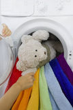 Woman taking toy from washing machine Stock Images