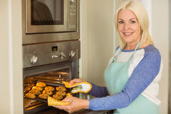 Woman taking tray of fresh cookies out of oven Stock Photos