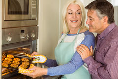 Woman taking tray of fresh cookies out of oven with husband Stock Photography