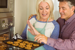 Woman taking tray of fresh cookies out of oven with husband Royalty Free Stock Photos