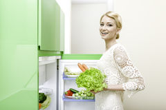 Woman taking vegetables out of fridge Stock Photography