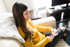 Woman Taking Vitamin Pills On Sofa. Unwell female brunette holding prescribed pills while relaxing at home royalty free stock photography