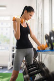 Woman taking weights from rack in fitness club Royalty Free Stock Photography