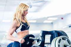 Woman taking weights from stand in fitness gym Stock Image