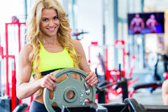 Woman taking weights from stand in fitness gym Royalty Free Stock Images
