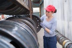 Woman taking wheel rim from racking. Wheel Stock Photo