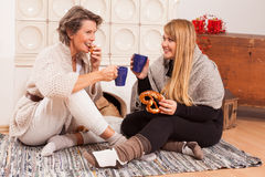 Woman talk between generations. Conversation between two women of different generations with a cup of hot drink and pastries sitting on the floor in front of a Stock Photo