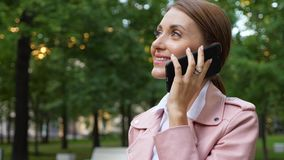 Woman talk on mobile phone outside, face close up. Against green park stock video footage