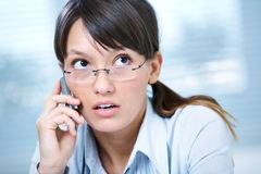 Woman talk  the phone. Young brunette in glasses anxiously on the phone in office Stock Photos