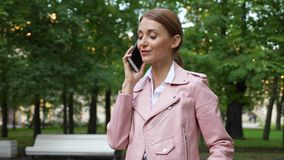 Woman talk on phone in green park stock video footage