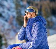 Woman talk by phone on mounting ski resort Stock Images