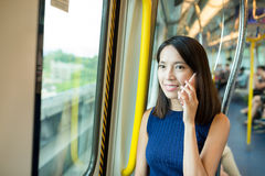 Woman talk to mobile phone in train Royalty Free Stock Images
