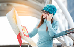 Woman talk to smartphone and looking map. In the city Stock Photos