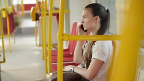 Woman talk to smartphone in the public transport, girl talking on the phone in the urban bus. HD stock video footage