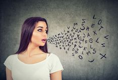 Woman talking with alphabet letters coming out of her mouth. Communication, information concept stock image