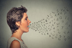 Woman talking with alphabet letters coming out of her mouth royalty free stock photo