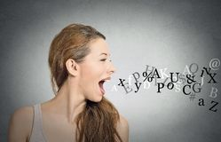 Woman talking with alphabet letters coming out of mouth. Side view portrait woman talking with alphabet letters coming out of her open mouth isolated grey wall Stock Images