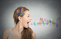 Woman talking, alphabet letters in her head coming out of mouth. Side view portrait woman talking with alphabet letters in her head and coming out of her open royalty free stock images