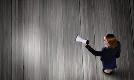 Woman talking in bullhorn Stock Photo