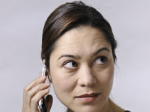 Woman talking on Cell phone. This asian young lady looking upwards and talking on the telephone Stock Images