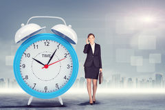 Woman talking on cell phone with big alarm clock Stock Photo