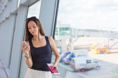 Woman talking by cell phone with boarding passport Stock Image