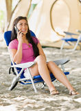 Woman talking on cell phone at campsite Stock Images