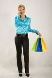 Woman talking by cell phone and holding paper bags Stock Photo