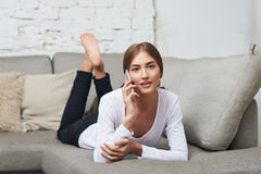 Woman talking on cell phone lying on couch Royalty Free Stock Photo