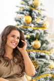 Woman talking cell phone near christmas tree Royalty Free Stock Photography