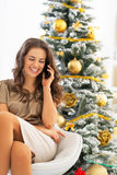 Woman talking cell phone near christmas tree Royalty Free Stock Image