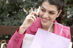 Woman Talking on Cell Phone Outdoors. Fashionable young woman sitting down on a bench in a shopping street, using a cell phone Royalty Free Stock Photography
