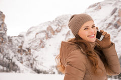 Woman talking cell phone outdoors among snow-capped mountains Royalty Free Stock Image