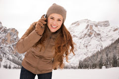 Woman talking cell phone outdoors among snow-capped mountains Stock Photos