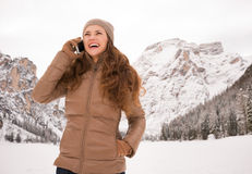 Woman talking cell phone outdoors among snow-capped mountains Stock Image