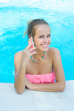 Woman talking on cell phone in the pool Stock Photo