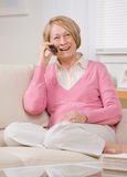 Woman talking on cell phone on sofa at home Royalty Free Stock Photos