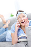 Woman talking on cell on a sofa Royalty Free Stock Image