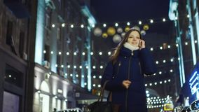 Woman talking on a cell, walking on evening city. Woman talking on a cell, the background blurry lights, windows, and expensive cars stock video