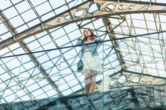 Woman talking on cellphone at airport with glass ceiling Stock Photography