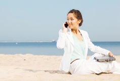Woman talking on cellphone on a beach Royalty Free Stock Images