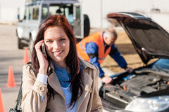 Woman talking on cellphone after car breakdown. Trouble problem mechanic Royalty Free Stock Image